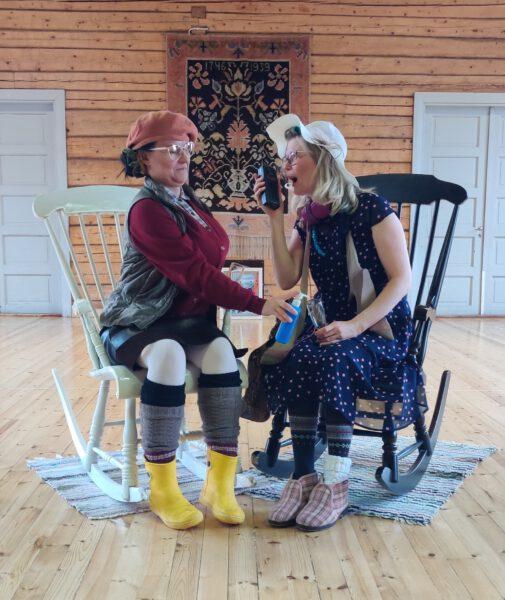Vähikkälän kylävideon näyttelijöitä pukeutuneena mummoiksi isot kännykät kädessä.