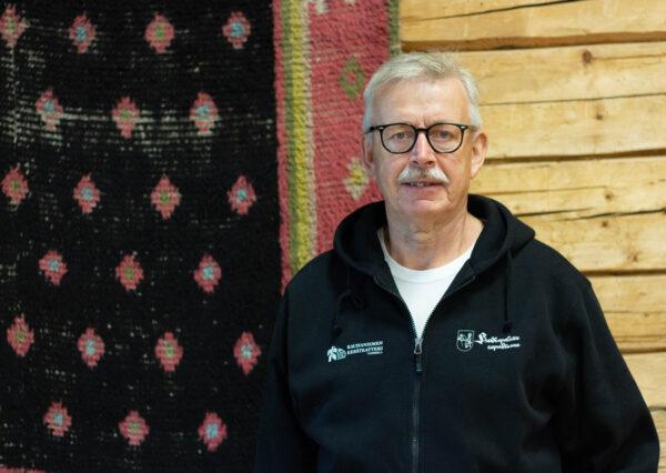 Jouko Lehtonen, mies seisoo vanhassa hirsitalossa sisällä ryijyn edessä.