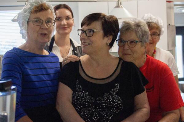 Viisi naista katsoo kameraan keittiössä hymyillen.