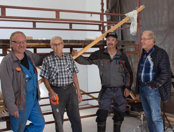 Miehet poseeraavat remonttihommien keskellä.
