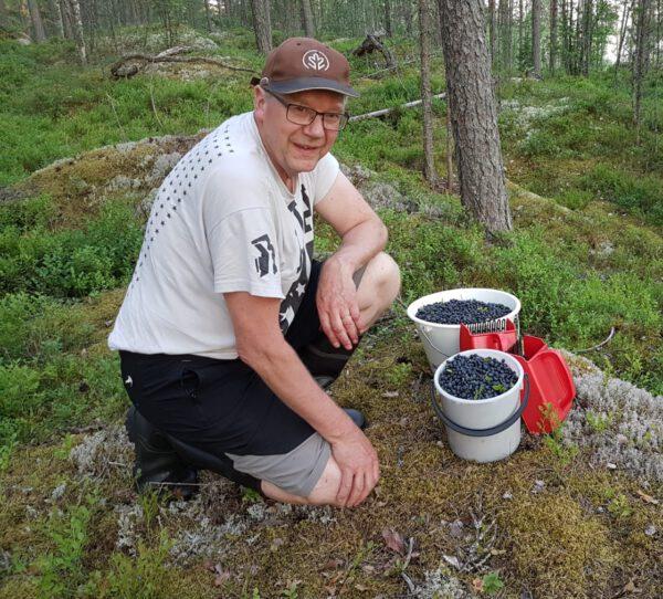 Mies poseeraa kameralle marjasankojen kanssa metsässä.