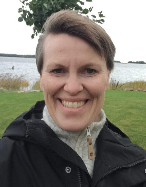 Nainen hymyilee rannalla.