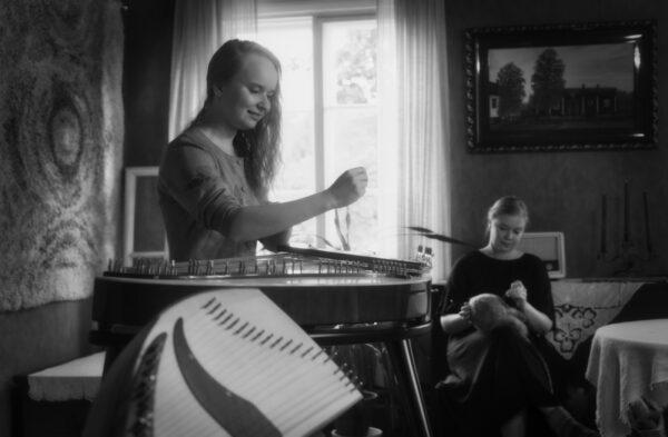Nainen soittaa kanteletta ja toinen nainen tekee villahuovutustyötä vanhan kartanon salissa.