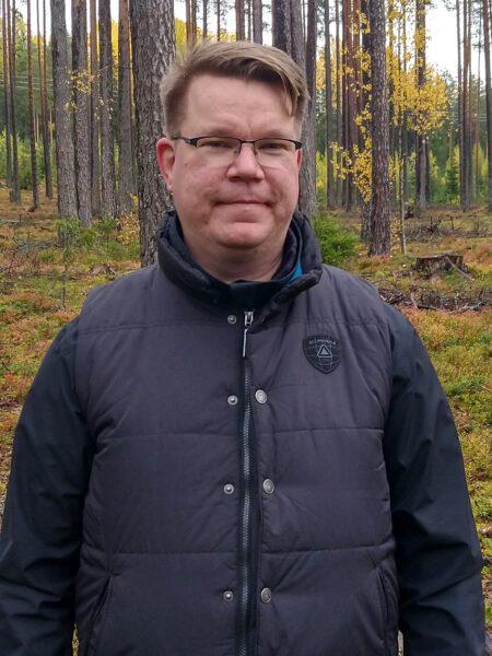 mies metsässä katsoo kohti kameraa.