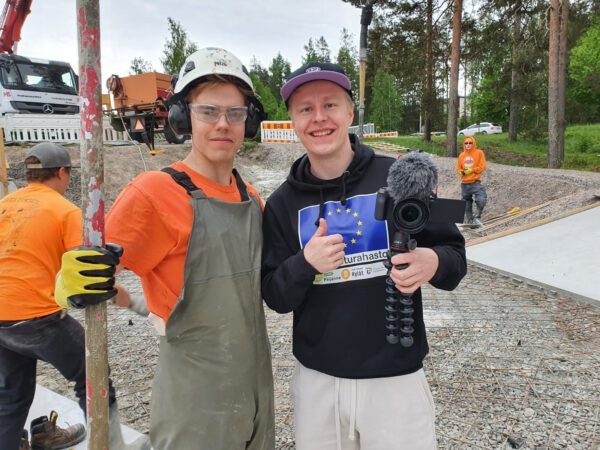 Kaksi poikaa kameran kanssa työmaalla katsoo kameraan ja hymyilee. toisella kädessä videokamera.