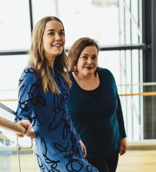Kaksi naista hymyilee portaissa.
