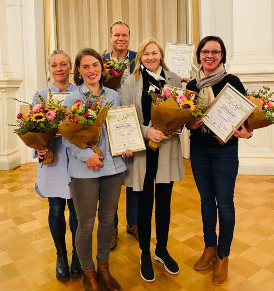 Neljä naista ja yksi mies hymyilee kuvassa kukkapuskat ja kunniakirjat kädessä.